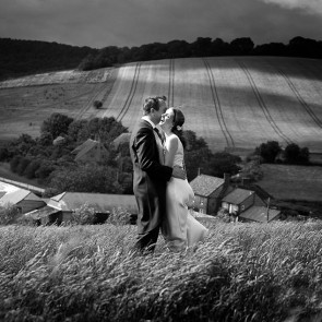 A wedding photo in the fields surrounding Upwaltham Barns wedding venue in Sussex