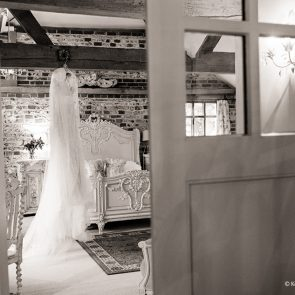 A bridal gown hangs from the beams of the Jasmine Cottage at Upwaltham Barns