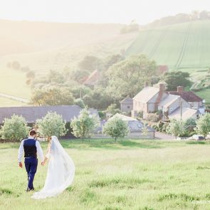 A bride and groom enjoy a walk in the countryside at this Sussex wedding venue