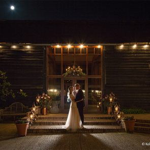 The bride and groom have a photo outside the East Barn at Upwaltham Barns