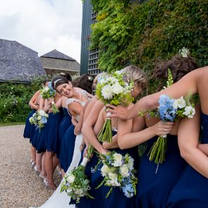 A bride and her navy bridesmaids at Upwaltham Barns wedding venue