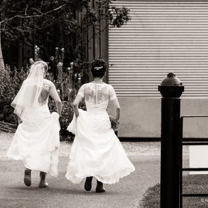 Two brides run down the lane on their wedding day at Upwaltham Barns