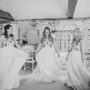 Bridesmaids twirl in their bridesmaid dresses at Upwaltham Barns wedding venue in Sussex