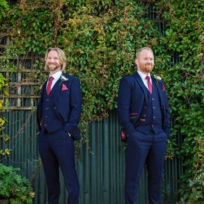 The groom and his groomsman wear navy wedding suits at Upwaltham Barns