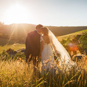 Husband and wife enjoy a sun set over Upwaltham Barns wedding venue in Sussex