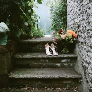 Wedding shoes and a bridal bouquet on the stairs at Upwaltham Barns in Sussex