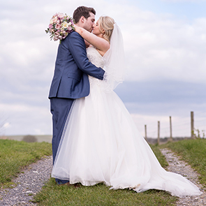 Husband and wife embrace for a kiss in front of the beautiful countryside at their Sussex wedding venue