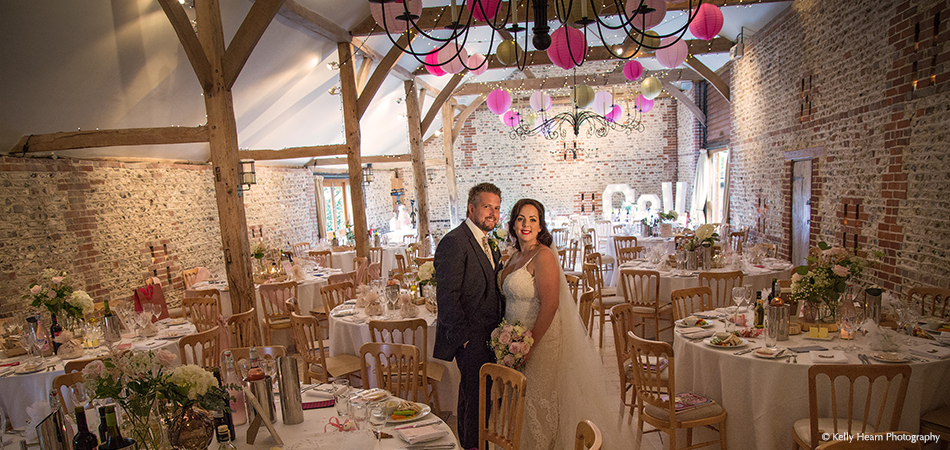 The bride and groom take in the stunning set up of their barn wedding reception at Uplwaltham Barns in Sussex