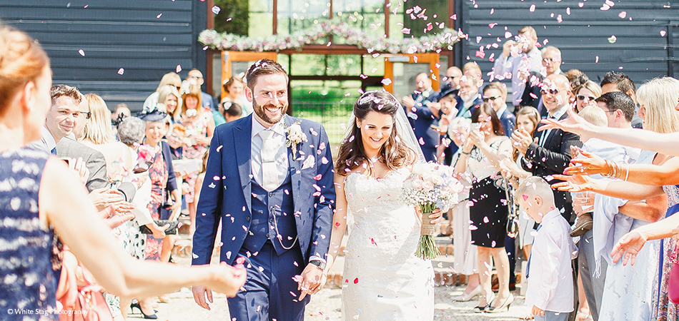 The bride and groom enjoy their confetti moment outside the barn at the wedding venue in Sussex