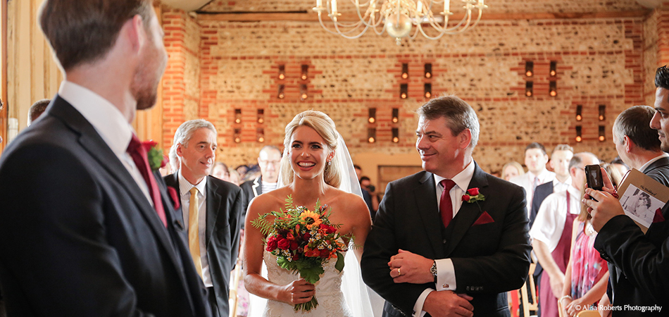 A bride walks down the aisle at the wedding ceremony in the East Barn