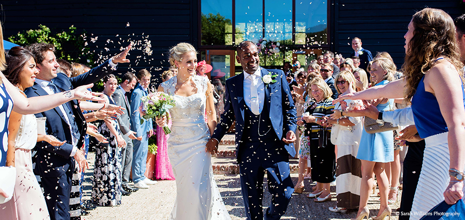 Wedding guests throw confetti at the newlyweds after their civil ceremony at Upwaltham Barns