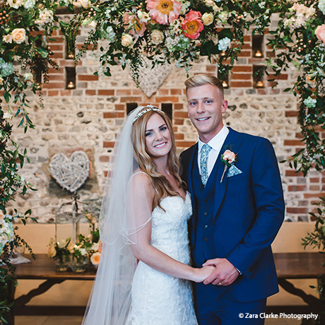 The newlyweds stand under a stunning floral wedding arch after their civil ceremony in Sussex