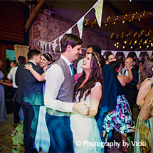 The happy newlyweds party the night away with their guests at the evening wedding reception in the South Barn