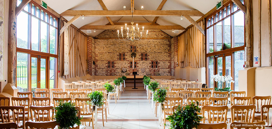 The rustic wedding barn is set up for a gorgeous civil ceremony at Upwaltham Barns in Sussex
