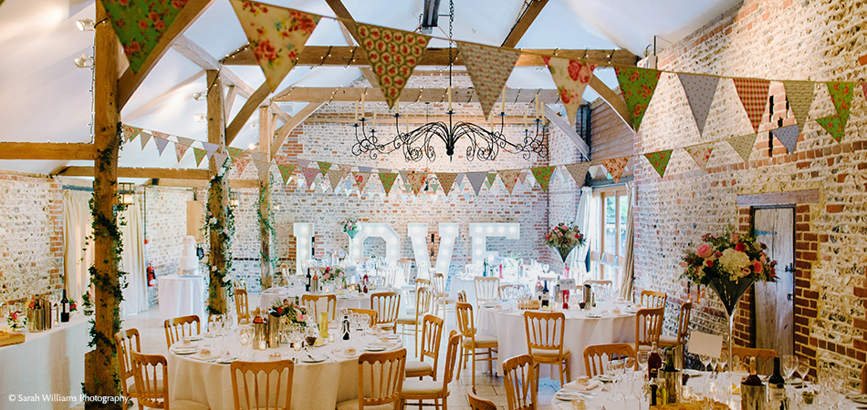 A country wedding theme included bunting in the South Barn at Uplwaltham Barns in Sussex