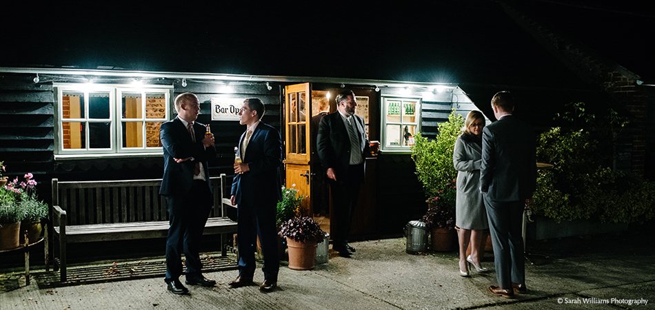 In the courtyard wedding guests mingle with their drinks outside the Stable Bar