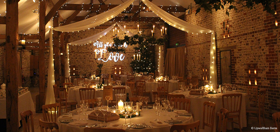 The gorgeous South Barn is adorned with fairy lights for a cosy evening barn wedding reception