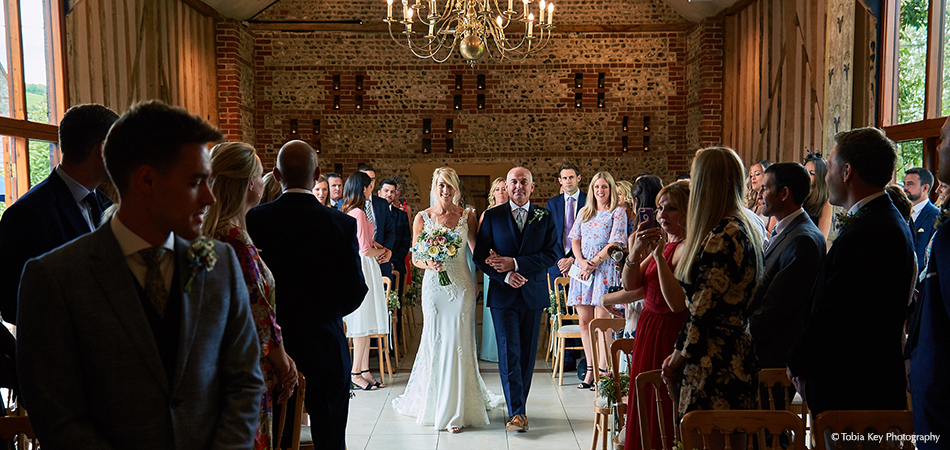 The bride and her father make their entrance to the wedding ceremony in the East Barn at Upwaltham Barns