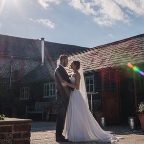 The couple are outside a barn wedding and Upwaltham Barns wedding venue in Sussex was perfect