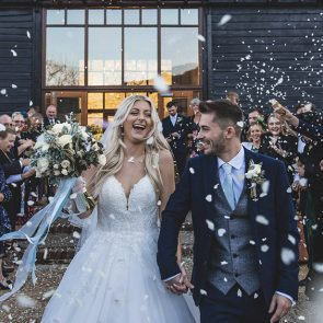 Guests throw wedding confetti over the newlyweds after their wedding ceremony at Upwaltham Barns