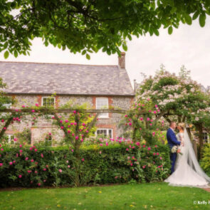 Bride and groom sharing a moment in the garden of Upwaltham Barns