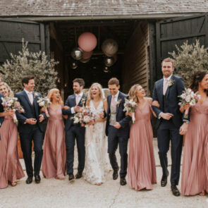 Bride and groom with their bridesmaids and best men in the courtyard at Upwaltham Barns