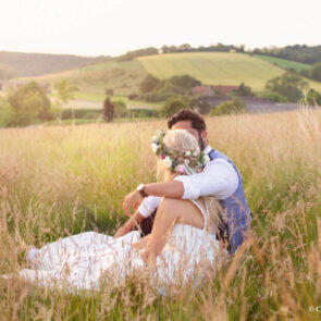 Bride and groom sharing a moment in the hills above Upwaltham Barns