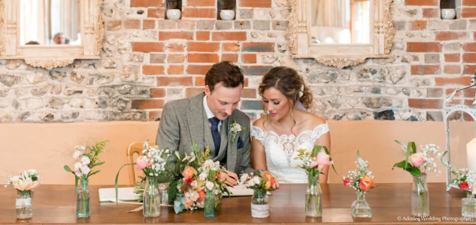 Couple signing the wedding register at Upwaltham Barns in Sussex