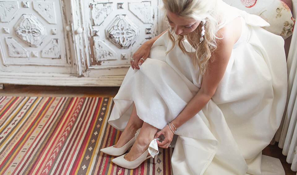 Bride putting on her wedding shoes at Upwaltham Barns