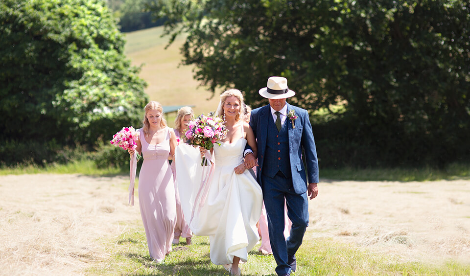 Bridal party walking to the ceremony at Upwaltham Barns
